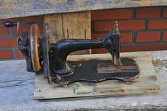Stara szwalna maszyna na drewnianej ławce zdjęcie royalty free