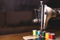 Stara szwalna maszyna z colour nicią na starym grungy praca stole, Krawiecki ` s pracy stół tkanina lub świetny sukienny robić pr obrazy stock