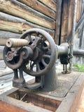 Stara szwalna maszyna z manuał przejażdżką, Zakrywający z korodowaniem, pyłem i pajęczynami, Przeciw tłu drewniana zaniechana sta Obraz Royalty Free