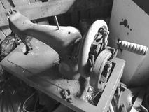 Stara szwalna maszyna z manuał przejażdżką, Zakrywający z korodowaniem, pyłem i pajęczynami, Przeciw tłu drewniana zaniechana sta Obrazy Royalty Free