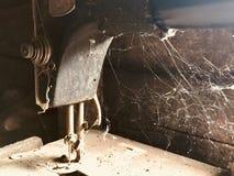 Stara szwalna maszyna z manuał przejażdżką, Zakrywający z korodowaniem, pyłem i pajęczynami, Przeciw tłu drewniana zaniechana sta Zdjęcia Stock