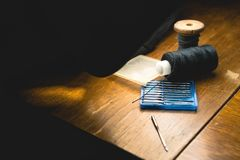 Stara szwalnej maszyny igła z czarną nicią na starym grungy praca stole, Krawiecki ` s pracy stół tkanina lub świetny sukienny ro obrazy stock