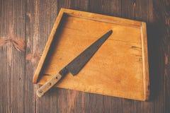 Stara tnąca deska, kuchenny nóż na drewnianym stole, rocznik projektujący Obraz Stock