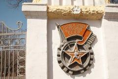 Stara USSR ściany ulga, biegacz w gwiazdzie Bawi się emblemat z flaga obraz stock