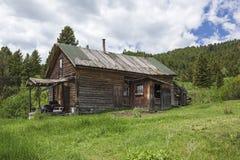 Stara wietrzejąca dom wiejski gór trawa Fotografia Stock