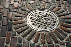 Stara wodna manhole pokrywa w brukowiec ulicie Obraz Royalty Free