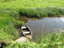 Stara zalewająca drewniana łódź w rzecznej zatoczce blisko wybrzeża, zakrywającego z trawą, na pogodnym letnim dniu obraz stock