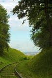 Stara zaniechana linia kolejowa wśród zalesionych wzgórzy zdjęcia royalty free