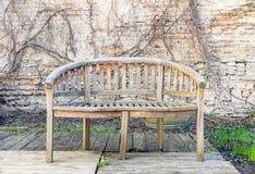 Stara zaniechana plenerowa ławka w tle wietrzejąca ściana z cegieł i suszy rośliny fotografia stock