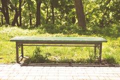 Stara zielona parkowa ławka na tle zieleni drzewa obraz stock