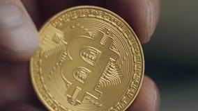 Staranne ręki i zły manicure Mężczyzna trzyma złotego bitcoin Na tle zamazujący laptop Pojęcie zbiory wideo