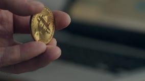 Staranne ręki i zły manicure Mężczyzna trzyma złotego bitcoin Na tle zamazujący laptop Pojęcie zdjęcie wideo
