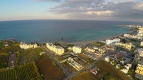 Staranni jarzynowi pola, nowożytni hotelowi budynki przy nadmorski w Cypr, widok z lotu ptaka zbiory wideo