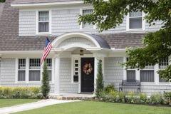 Staranny i dosyć shingled retro dom z łukowatym entryway i piękny kształtować teren z kolorowym lato wiankiem na dzwi wejściowy i obrazy stock