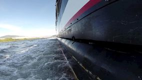 Starboard side of a sailing vessel moving down river stock video