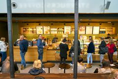 Starbucks. DUSSELDORF, GERMANY - CIRCA SEPTEMBER, 2018: people staying in queue at counter service a Starbucks coffeeshop in Dusseldorf airport stock image