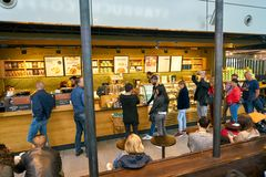 Starbucks. DUSSELDORF, GERMANY - CIRCA SEPTEMBER, 2018: people staying in queue at counter service a Starbucks coffeeshop in Dusseldorf airport stock photography