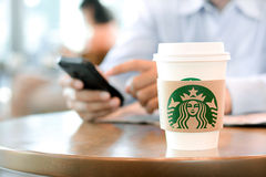 Starbucks take away coffee cup on the table Royalty Free Stock Photo