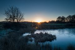 A starburst of dawn light breaking on a frozen pond on Wetley Moor. royalty free stock image