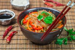 Starch rice, potato noodles with vegetables - bell peppers, carrots, cucumber, sesame seeds, cilantro and soy sauce. Vegetarian dish. A delicious lunch or royalty free stock photo