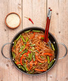 Starch rice, potato noodles with vegetables. Bell peppers, carrots, green beans, onions, sesame seeds and soy sauce. Vegetarian dish. A delicious dinner in stock images