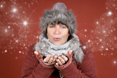 Stardust. Happy woman blowing stardust in winter season over red background Royalty Free Stock Photos
