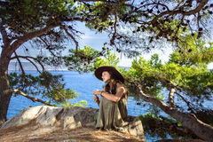 Stardust on sea coast. Reverie young girl sitting in a forest on seaside Stock Photo