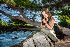 Stardust on sea coast. Reverie young girl sitting in a forest on seaside Stock Image