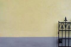 Stare żelazo bramy malowali w kolorze żółtym z błękitną ścianą Zdjęcia Stock