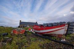 Stare czerwone i białe łodzie rybackie wśród plażowego zagracenia Fotografia Stock