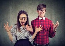 Stare di grido sollecitato delle coppie arrabbiate disperate vicino ad a vicenda fotografia stock