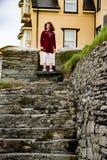 Stare di sguardo e sorridente del giovane ritratto della bambina in cima alle scale rocciose Fotografia Stock