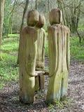 Stare ha scolpito le figure che circondano il banco sulla passeggiata del terreno boscoso immagine stock libera da diritti