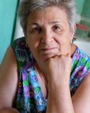 Stare kobiety myśleć indoors z jej ręką na podbródku Zdjęcia Royalty Free
