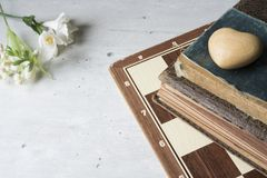 Stare książki z szachową deską, kwiatami i sercem, zdjęcia stock
