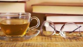 Stare książki i gorąca czarna herbata w szklanym kubku na półce zbiory