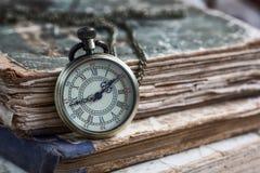 Stare książki i kieszeniowy zegarek obrazy royalty free