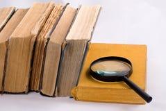 Stare książki i magnifier Zdjęcia Royalty Free