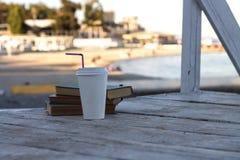 Stare książki na plaży z biorą oddaloną kawę Zdjęcia Royalty Free