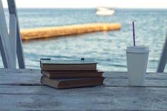 Stare książki na plaży z biorą oddaloną kawę Fotografia Royalty Free