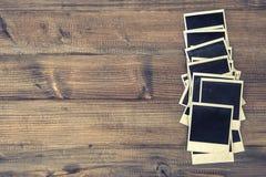 Stare natychmiastowe fotografii ramy na nieociosanym drewnianym tle Zdjęcie Royalty Free