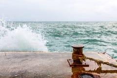 Stare ośniedziałe cumownicy na molu fala łamają na jetty Zdjęcia Royalty Free