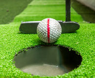 Stare piłki golfowe i putter na sztucznej trawie Zdjęcie Stock