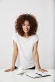 Stare sorridente di signora africana di affari nel luogo di lavoro Priorità bassa bianca Fotografia Stock Libera da Diritti