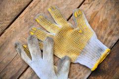 Stare zbawcze rękawiczki na drewnianym tle, rękawiczki na brudnych robotach Obrazy Royalty Free