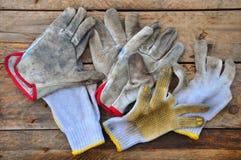 Stare zbawcze rękawiczki na drewnianym tle, rękawiczki na brudnych robotach Obraz Stock