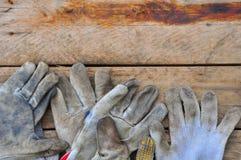 Stare zbawcze rękawiczki na drewnianym tle, rękawiczki na brudnych robotach Fotografia Stock