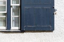 Starego Błękitnego obieranie farby rocznika Nadokienna żaluzja na biel ścianie zdjęcie royalty free