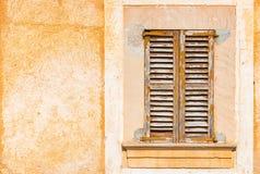Starego brązu drewniana nadokienna żaluzja z rusti tynku ściany tłem zdjęcie stock