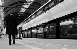 Starego człowieka odprowadzenie z jego kierowniczym puszkiem wzdłuż pociągu na pustej platformie w czarny i biały obraz stock